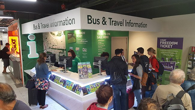people standing in front of a bus and travel information desk at dublin airport