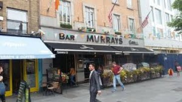 Exterior of Murray's Bar with flower pots and a terrace