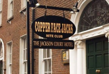 Copper Face Jacks Nite Club entrance with Black and Yellow Sign Hanging Over Green Door