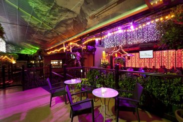 Dtwo Nightclub Interior with Tables, Hanging Fairy Lights and Greenery