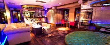 Inside of Krystle Nightclub with White Leather Sofas, Chandelier, Bar, Green Loveseat and Mood Lighting Luxurious