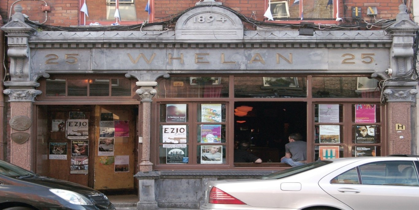 Entrance of Whelan's Bar/Pub With many Posters in Window and Cars Parked Out Front