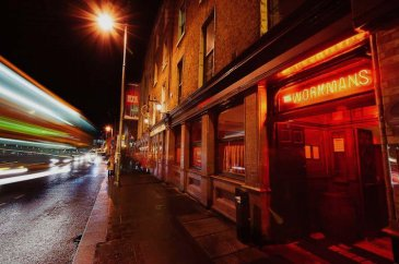 Entrance of Workman's Bar with Red Neon Lights and Buses Flashing By In The Night