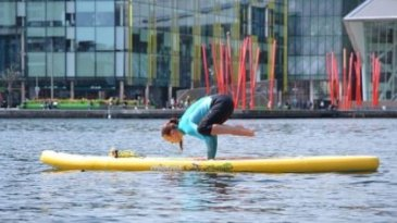 Lady practising yoga on stand up paddle board in grand canal basin dublin