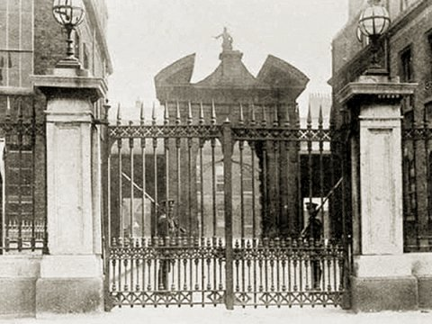 black and white photo of the gates t Dublin castle with two guards