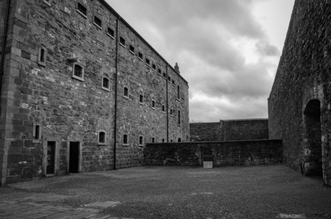 black and white photo of the wall in kilmainham gaol in dublin