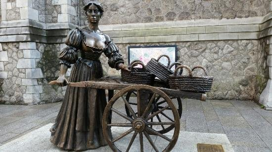 Molly Malone Statue and Cart with St. Andrew Church in background