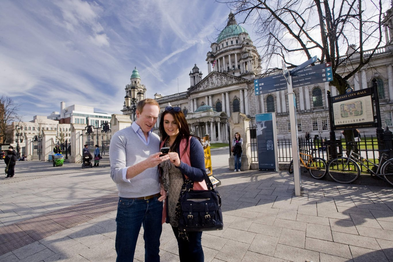 Couple of tourists checking phone outside Belfast City Hall