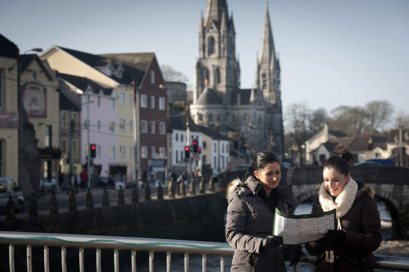 Two friends look at a map while sightseeing in Cork