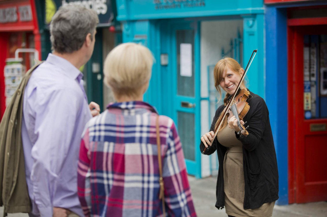 Couple enjoying a busker playing a fiddle on Galway's Shop Street on a day tour from Dublin