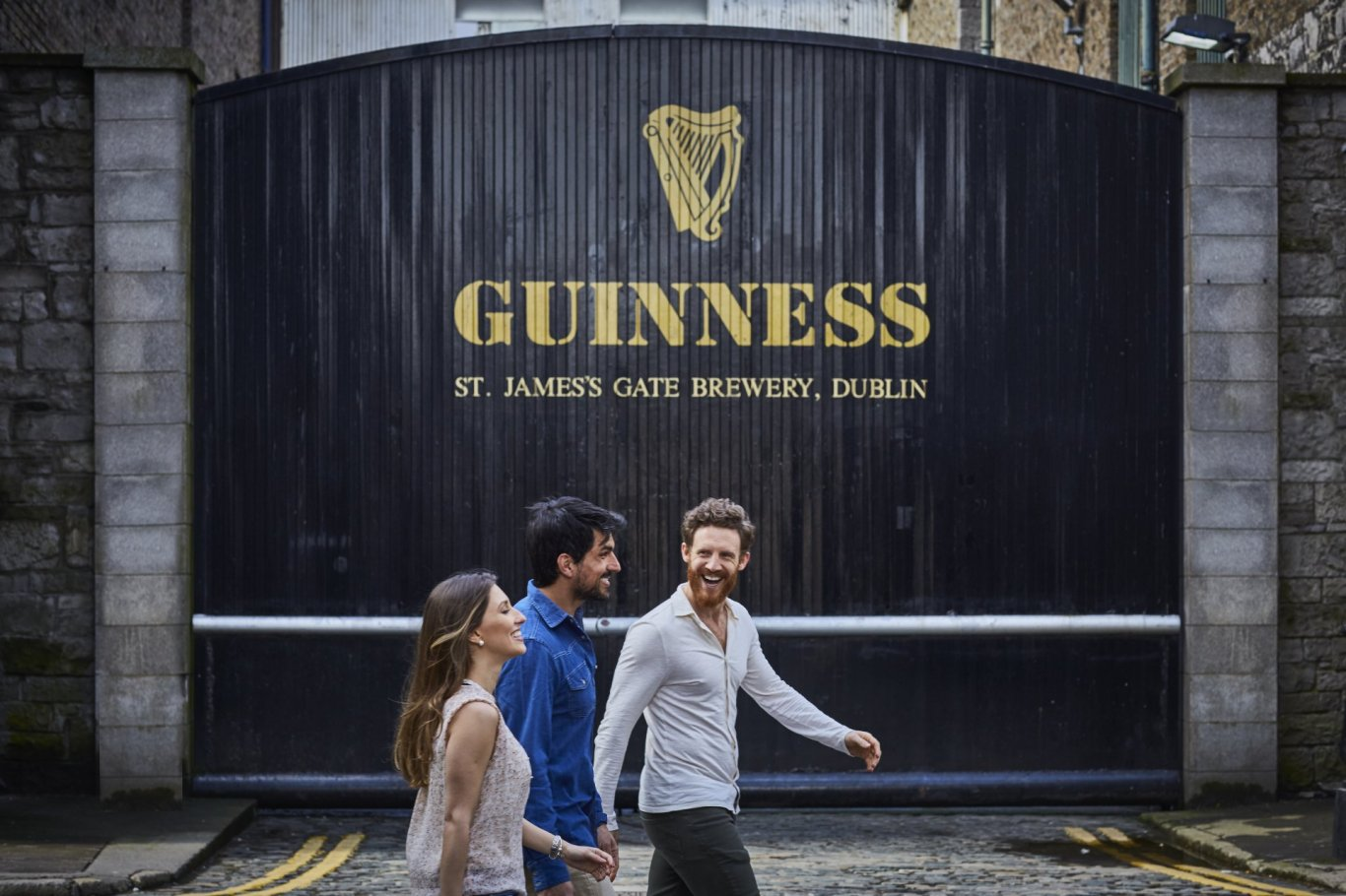 people walking in front of guinness factory