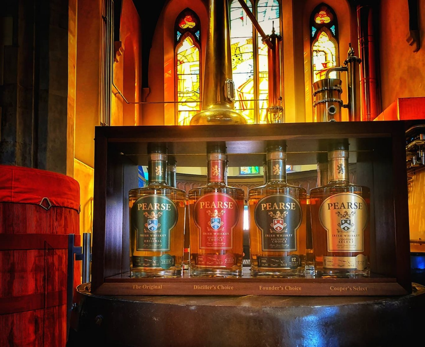 Four bottles of Pearse Lyons Irish Whiskey on whiskey barrel in Pearse Lyons Distillery