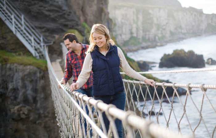 Couple look over edge while crossing carrick-a-rede rope bridge