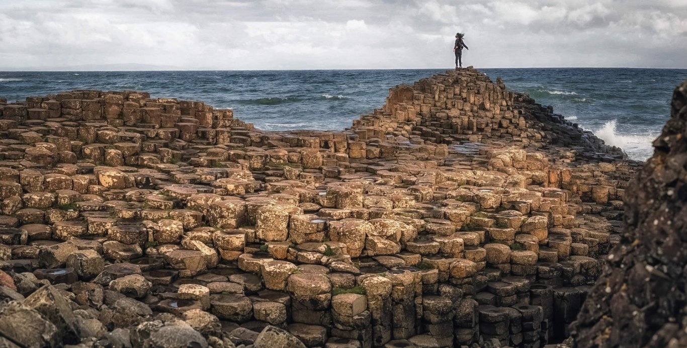 Person on giants causeway rocks while waves crash against shore