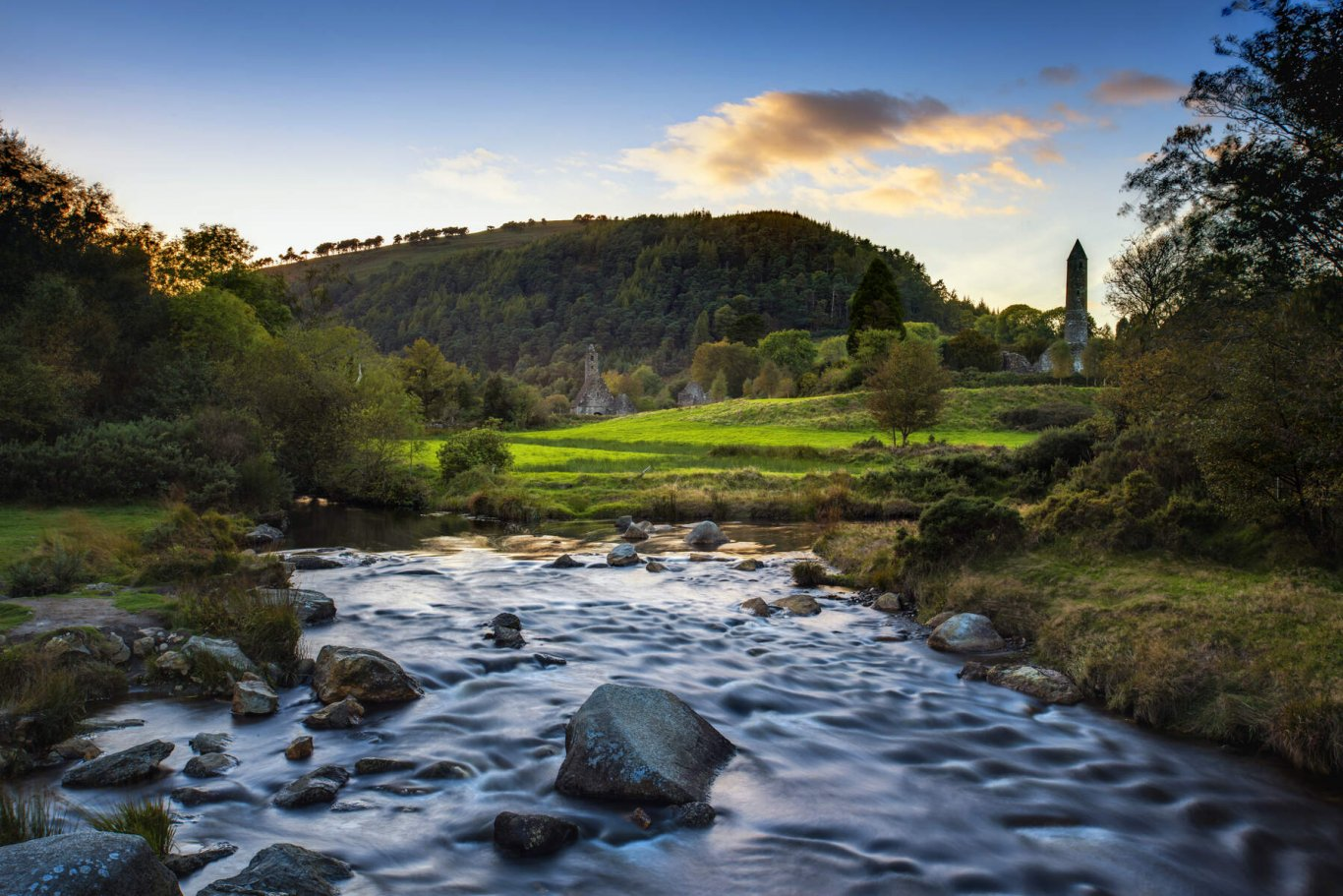 Flowing river with Glendalough round tower and wicklow national park
