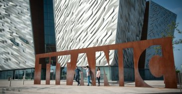 Group of friends pose for photo outside Titanic Centre Belfast